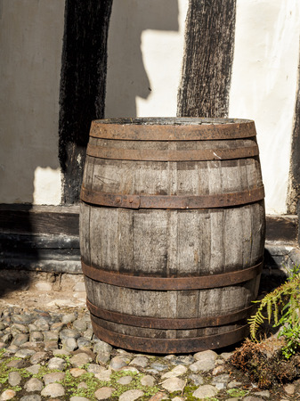 standing alone: Large traditional oak barrel standing alone in a courtyard. Stock Photo