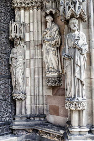 statutes: Three religious statues on a church wall next to the doorway.
