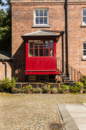 redbrick: Vertical shot of  old courtyard with redbrick house and iron steps leading to a red porch Stock Photo