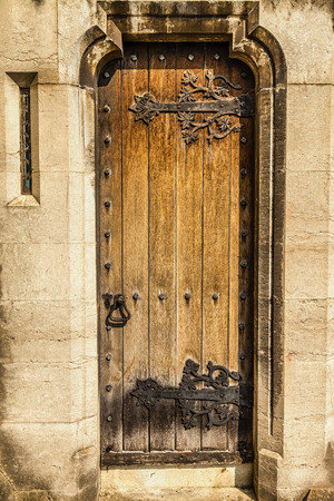 door leaf: Ornate Victorian Church door  complete with leaf pattern hinges, shapely keyhole, iron door knocker, and slit window built into a stone wall.