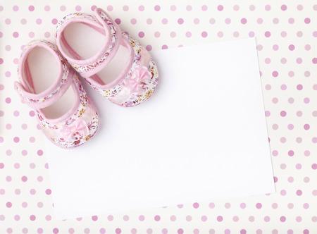 Blanco kaart met baby meisje schoenen op een pastel roze gevlekte achtergrond.