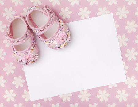 Lege kaart met baby meisje schoenen op een pastel roze bloemen achtergrond.