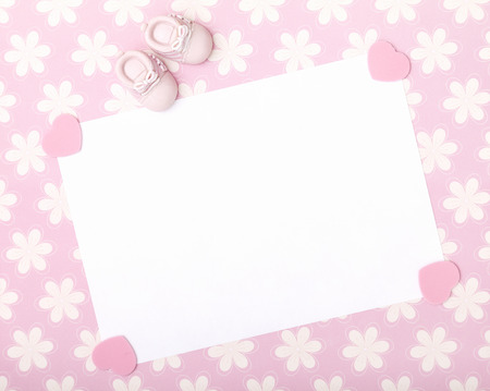 blank card with baby girl shoes on a pastel pink floral background