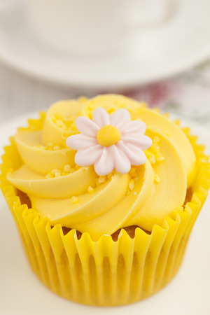 cream swirl: Close up of a Lemon cupcake with butter cream swirl and fondant flower. Stock Photo