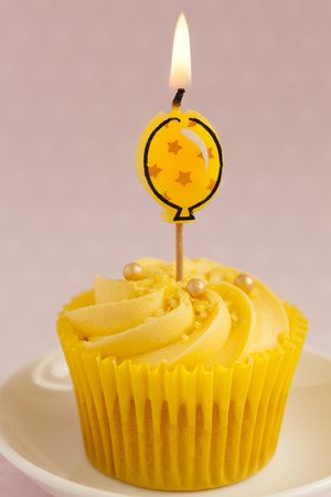 cream swirl: close up of Lemon cupcake with butter cream swirl and  single yellow alight balloon candle Stock Photo