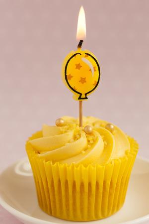 alight: stretta di Cupcake Limone con ricciolo crema di burro e unico giallo candela accesa pallone Archivio Fotografico