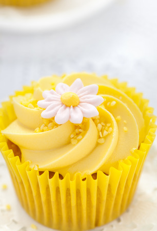 cream swirl: Close up of a Lemon cupcake with butter cream swirl and fondant flower decorations Stock Photo
