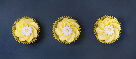 small group of objects: Aerial view of three lemon cupcakes with fondant flower in single file on a blue slate  background.