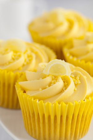 cream swirl: Close up of Lemon cupcakes with butter cream swirl and candid fruit. Stock Photo