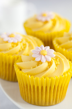 Close up of Lemon cupcakes with butter cream swirl and fondant flower. photo