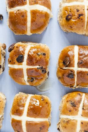 Hot cross buns, Ariel view of spiced sweet bread coated in sweet honey in rows on baking sheet paper