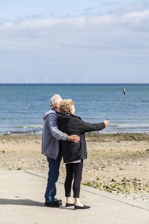 september 9th: Llandudno, Wales, UK. 9th September, 2015  elderly couple taking selfies using a selfie stick on Llandudno beach