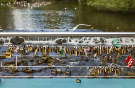 derbyshire: Bakewell, Derbyshire, England, UK - July 19, 2015: Love locks attached to the cable on weir bridge, Bakewell, Derbyshire, England, UK,