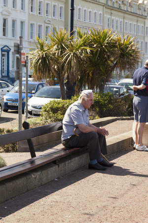 exhaustion: Llandudno, Wales, UK - May 17, 2014: Elderly man appears to be suffering from heat exhaustion protects his balding head with a knotted handkerchief from the hot sunshine whilst sitting on wooden bench.