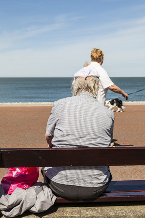 Llandudno, Wales, UK - May 17, 2014: Elderly man protects his balding head with a knotted handkerchief from the hot sunshine whilst sitting on wooden bench on Llandudnos north promenade in Wales U.K