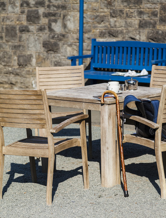 the milk jug: Outdoor table set with  silver teapot, milk jug ,teacups,  map, rucksack, and walking cane.