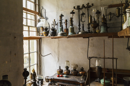 Many oil lamps gathering dust in dirty dusty room, illuminated with window light.
