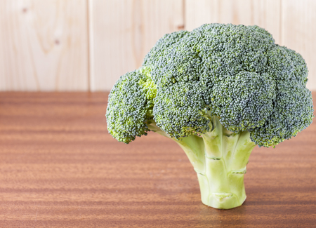 flowerhead: Broccoli  standing upright on red wood table with pinewood background.