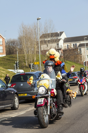cuddly toy: Stoke On Trent Staffordshire UK, Sunday 13 March 2016  Bikers with cuddly toys waving. Thousands of bikers travel through the streets of Stoke On Trent collecting  Easter eggs. Now in its 38th year the star bikers annual Easter egg run is a 14-mile route
