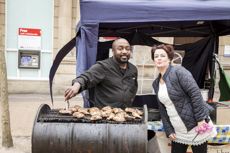 lyme: Newcastle Under Lyme England.- May 5 2014. Street food seller cooking chicken on barbecue and posing with woman marshal at the Lymelight Festival  Newcastle Under Lyme England.