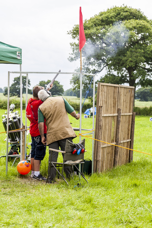 the royal county: The Royal Cheshire County Show,  Knutsford , England, UK. - June 22, 2016 : People clay shooting on the shooting range. Senior Male instructor assisting young man to shoot shotgun. Editorial