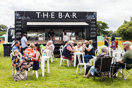 the royal county: The Royal Cheshire County Show,  Knutsford , England, UK. - June 22, 2016  People of all ages drinking beverages from a mobile licensed bar in an open field at the The Royal Cheshire County Show Ground. Knutsford , England, UK