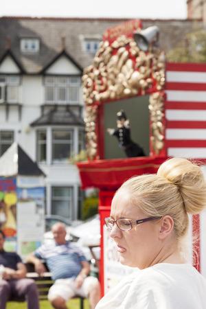 lengua afuera: Llandudno, Gales del Norte, Reino Unido. 18 de mayo de 2014: Mujer rubia joven con los ojos cerrados que llevaba gafas lamiendo la lengua a un teatro de marionetas. paseo de Llandudno.