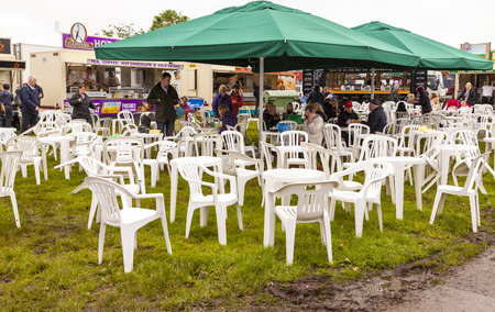 the royal county: The Royal Cheshire County Show,  Knutsford , England, UK. - June 22, 2016  People of all ages eating and drinking beverages in a muddy field. Knutsford , England, UK