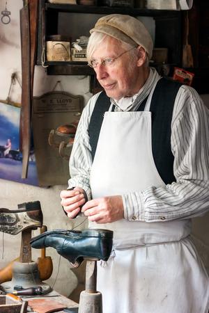 vestidos de epoca: IRONBRIDGE, Inglaterra - Julio 21 de 2012: Hombre vestido como zapatero victoriano volviendo a representar sus zapatos reparación de funciones en la colina de Blists Museo establecidos en calles recreados y es una atracción turística popular. Ironbriidge, Shropshire, Inglaterra.
