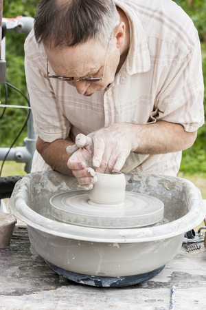 concentrate on: Stoke On Trent England - June 5 2011: Middle  aged man demonstrating his potting skills on a potters wheel at the Etruria Canals Festival, Stoke On Trent, Staffordshire, England.