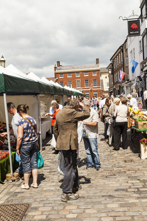 typically british: Leek, Staffordshire Moorlands, England, U.K - June 21 2014 : Shoppers at Leek�s open air market With down at heal man in foreground. Leek  is an ancient borough and was granted its royal charter in 1214. Editorial