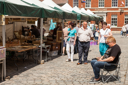 typically british: Leek, Staffordshire Moorlands, England, U.K - June 21 2014 : Shoppers at Leek�s open air market Leek  is an ancient borough and was granted its royal charter in 1214. Editorial