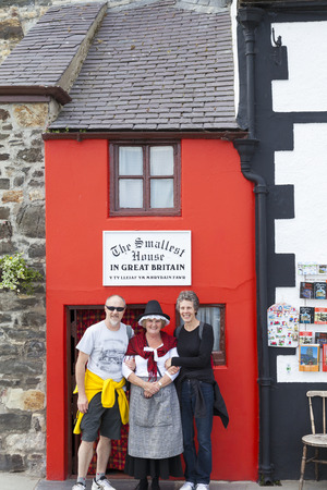 smallest: Conway, North Wales UK - May 18 2014 Tourists pose for picture with woman in traditional Welsh costume outside the smallest house in Great Britain.