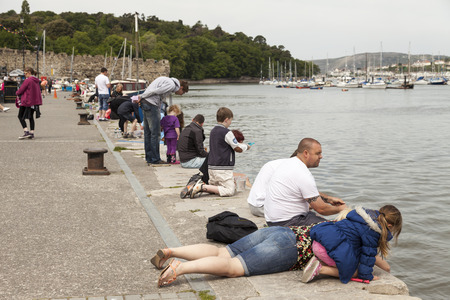 familias jovenes: Conwy, North Wales UK - May 18 2014 Young families crab fishing on the quay side in Conwy, North Wales. Editorial