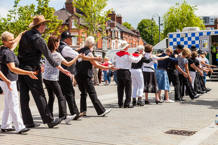Leek, Staffordshire, England, U.K - June, 21 2014 : People of all ages line dancing in the street as part of Leeks Country and Western weekend. Leek, Staffordshire, England. Editorial