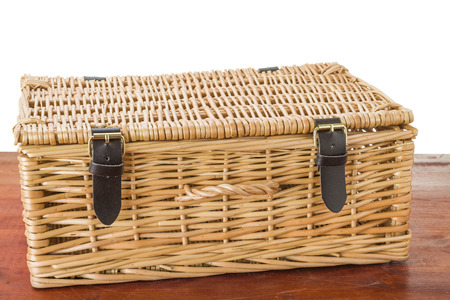 buckled: Wicker picnic basket with leather brass buckled straps sitting on mahogany wood table. Isolated on white.