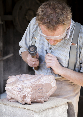 stonemasonry: Telford, England.- July 9th 2014:  Stone Mason  sculpting  a slab of granite. Dust, & stone fragments fly off into the air as he works the stone.