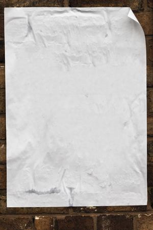 Textura de póster en blanco, arrugado, arrugado enroscado en los bordes pegados a una pared de ladrillos.