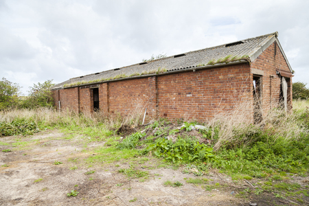 Derelict Farm Building, Abandoned agricultural red brick outbuilding . Stock Photo