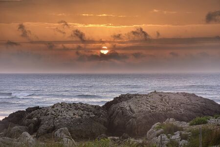 beautiful orange sunset over the blue sea and rocks Standard-Bild