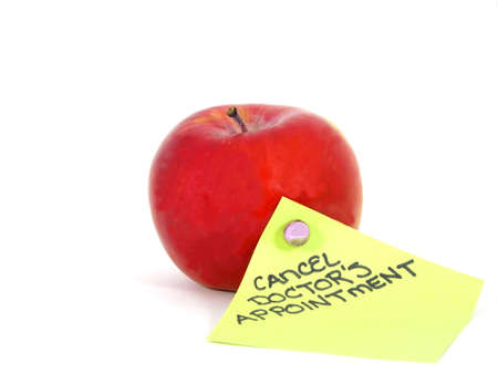 Macro photo of red apple and cancellation reminder on green note with white background