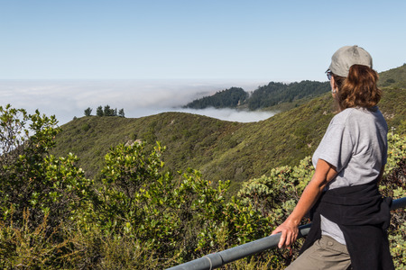 A female stop in the trail to admired the marine layer fog that is covering the Pacific Ocean in the San Francisco Bay Area. View form Mt. Tamalpais on a sunny but foggy day