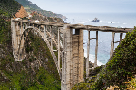 bixby: California Coastline near Big Sur, south of San Francisco, beautiful seascape with cloudy sky and colorful landscape and historic Bixby Bridge in highway 1
