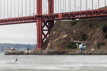 marin: A CHP helicopter flying under the Golden Gate Bridge near the rocks in Sausalito, Marin County Editorial