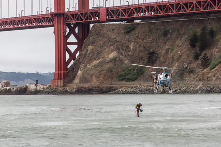 marin: A CHP helicopter flying under the Golden Gate Bridge near the rocks in Sausalito, Marin County and an officer diving into the water