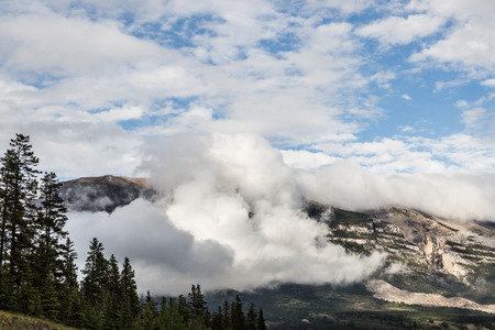 canmore: low big white cloud and a beautiful blue sky over the Canmore town in Alberta Stock Photo