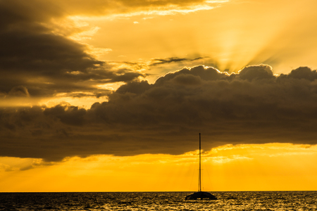 Beautiful scenic warm sunset at the beach in kiehi, Maui, Hawaii. Golden light of ray of sun covered by clouds Stock Photo