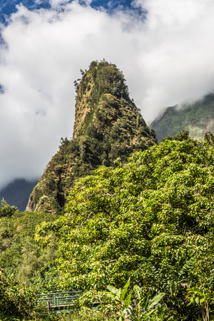 straight up: Iao Needle State Park in Central Maui. The Iao Needle is a solid green, needle-like mountain shooting straight up to the sky. Iao Valley State Park is located in Central Maui near Wailuku Stock Photo