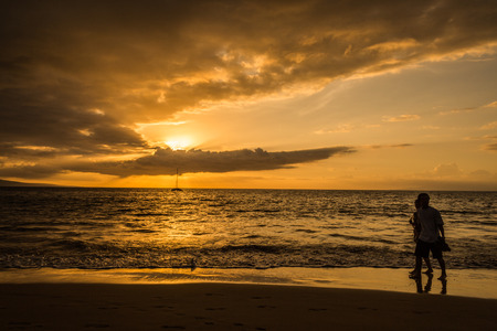 Tourist walking by the beach. Beautiful scenic warm sunset at the beach in kiehi, Maui, Hawaii. Golden light of ray of sun covered by clouds Stock Photo