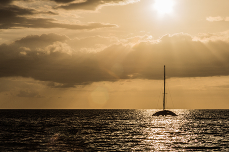 A Boat in the ocean at sunset. Silohuette scenery with beautiful sun ray scaping from the cloud covering the sun in Kihei, Maui